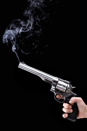 hand holding a revolver with smoking barrel, against black background Stock Photo