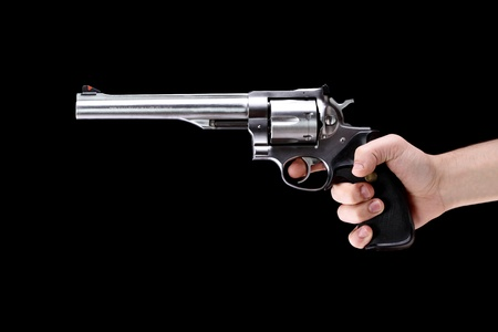 hand holding a revolver, aiming straight, against black background