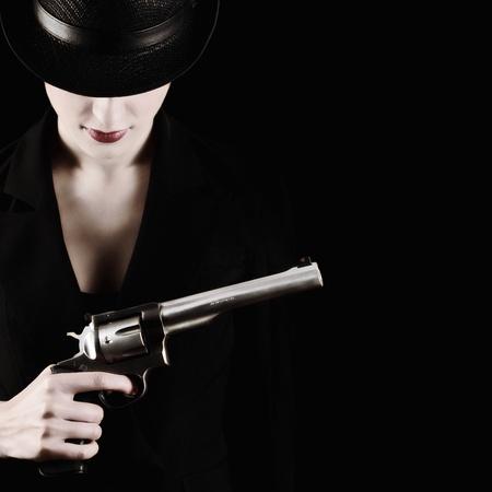 mujer con arma: elegante dama de negro con un revólver