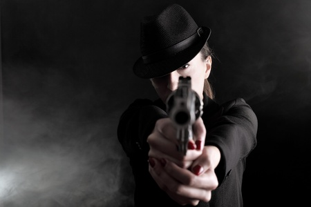 elegant lady in black holding a revolver  photo