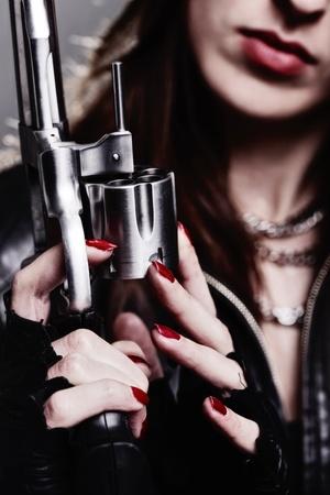 magnum: jeune fille rebelle avec des gants de moto d�tenant un revolver