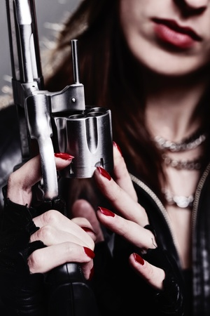 rebel girl with motorcycle gloves holding a revolver