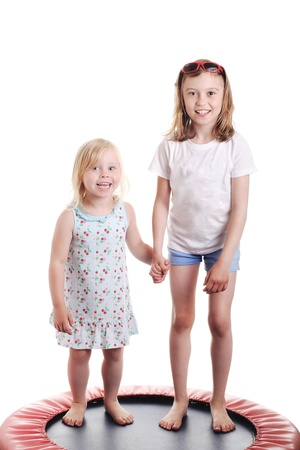 cute little girls holding hands on a trampoline, against white background photo