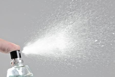bottle spraying perfume against gray background Banco de Imagens