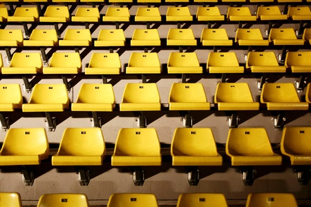 harsh: many yellow chairs with harsh light from side Stock Photo
