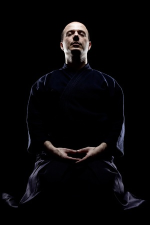 portrait of a kendo fighter meditating, against black backgroung Stock Photo