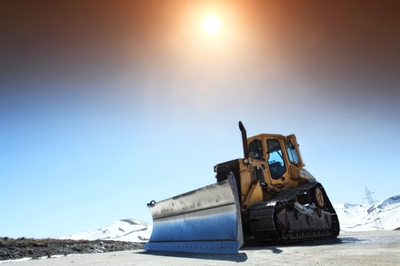 snow plow: snow cleaning bulldozer on a mountain road in spring