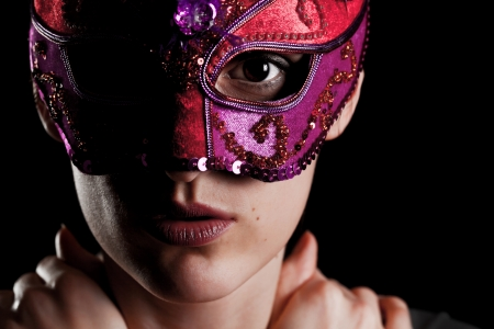Elegant young girl with carnival mask against black background Stock Photo