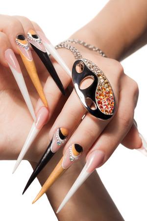 long nail: estremamente lunghe unghie con nail-art e gioielli di cristallo,