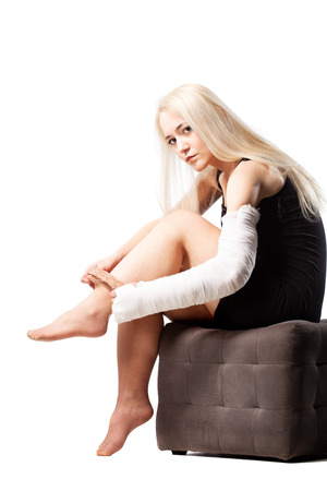 girl undressing: Blond girl with a broken arm in plaster, trying to put on stockings