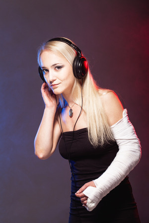 sexy headphones: sexy girl with broken arm listening music on headphones and dancing, disco smoke in the background Stock Photo
