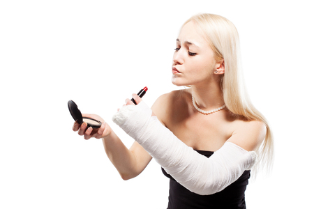 putting lipstick: Blond girl with a broken arm in plaster having trouble putting a lipstick