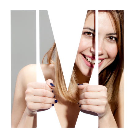 girl hiding behind and holding the letter M