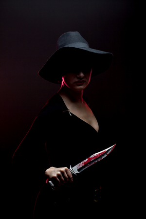 girl with a huge bloody knife in shadow, red backlight Stock Photo