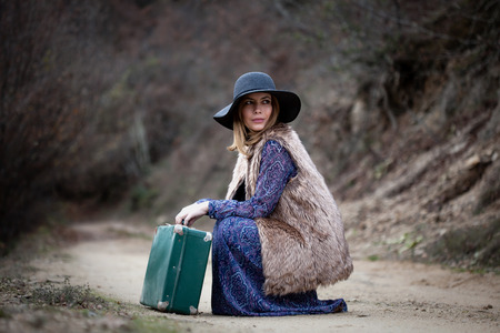 pretty young woman with a leather suitcase on a dirtroad in the mountains, vintage style Stock Photo