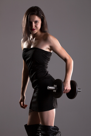 gym dress: Sexy girl in short black dress, posing and lifting weights