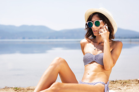 girl sunbathing and talking on a smart phone