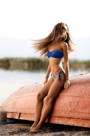 beautiful girl on an upturned rowboat with hair in the air Stock Photo