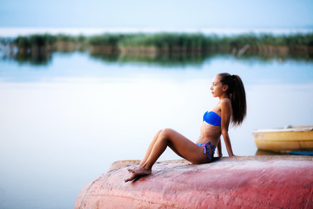 beautiful girl on a rowboat, sunset time on a lake. full body shot