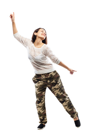 girl in camouflage pants dancing against white background