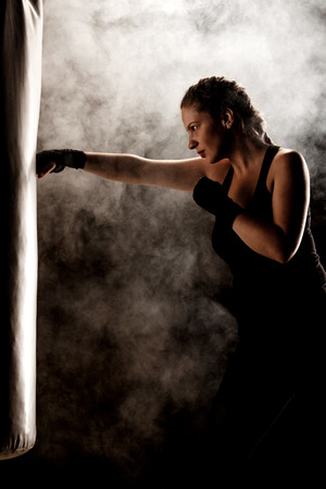 kick fighter girl punching a boxing bag Stock Photo