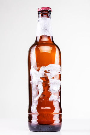 beer bottle with torn label isolated on white 写真素材