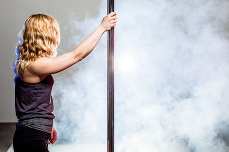 pole dance girl in a studio with white smoke in the background Banco de Imagens - 118230042