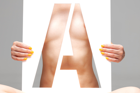 nude female body behind stencil letter a