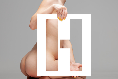 nude female body behind stencil letter h