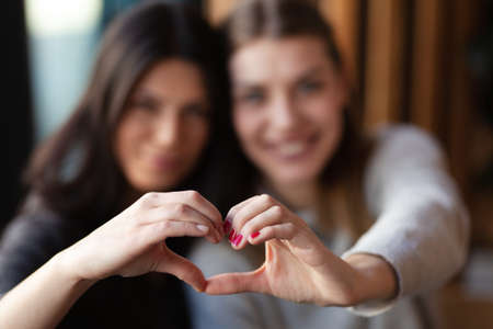 Two lovely girls smiling in a cafe and making a hearth shape with their hands. Focus on hand.