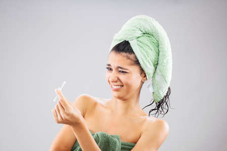 Beautiful young girl posing with towels after having a bath, holding cotton ear stick. Funny disgusted face expression.