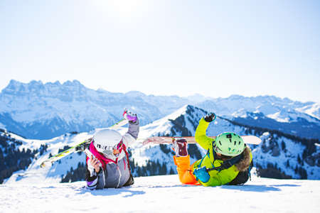 two female friends with ski and snowboard equipment having fun and high five with snow in the air.