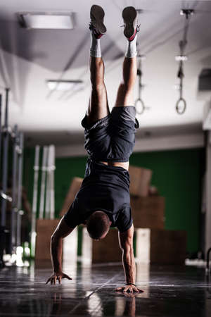 Muscular athlete standing and walking on hands upside down.