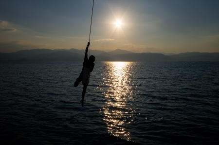 A guy uses a rope of a sailing yacht to swing and fly over the Aegean sea at dusk photo