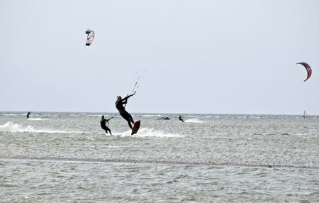 Kite-surfer jumping in ocean and windsurfer photo
