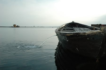 old boat at habour lets water out photo