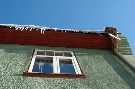 Icicles hanging from roof on green house photo