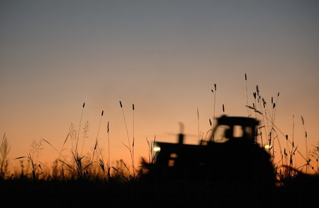 vintage tractor works on field at sunset     photo