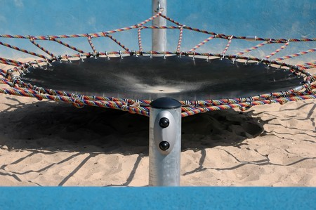 abstract trampoline detail on sandy playground