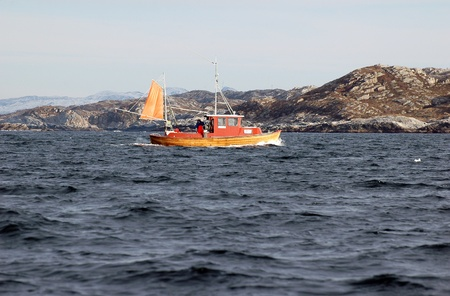 Fishing boat heading out to the ocean photo