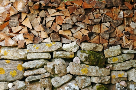 woodpile on stone wall photo