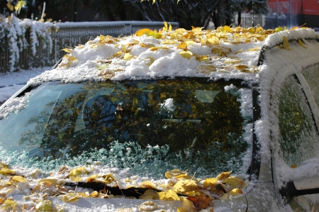 cars covered with snow and leaves at autumn