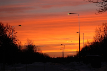 sunset in sky over street with lamps photo