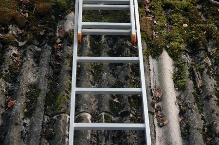 old demaged roof with moss and ladder photo