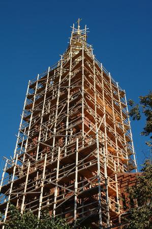 renovation of an church tower with golden cross