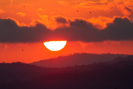 Landscape with red sun setting behind dark clouds and silhouette of hills and trees Stock Photo