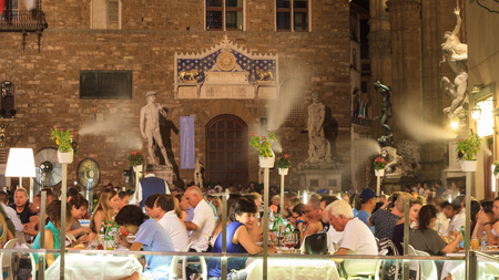 Florence, September 2016: Tourists to dinner at luxury restaurant with outdoor cooling misting system, in Piazza della Signoria, on September 2016 in Florence Sajtókép