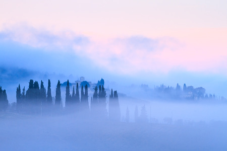 Tuscan landscape with country houses and cypresses in the autumn fog in Chianti, Tuscany, Italy