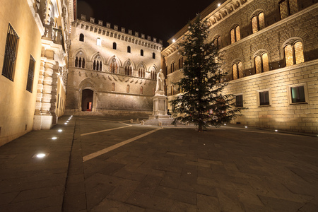 Siena, January 2016: Sallustio Bandini monument and  the main Gate of Monte dei Paschi Bank in Piazza Salimbeni with Christmas tree, on January 2016 in Siena, Tuscany, Italy Stock fotó - 109867215