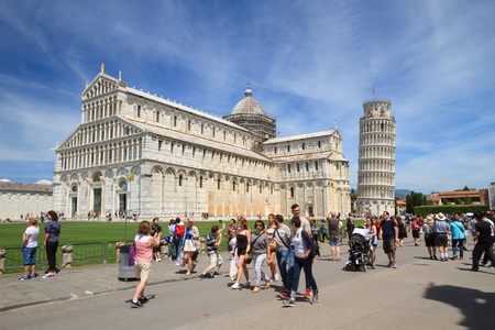 Pisa, May 2017: Tourists in Square of Miracles (Piazza dei Miracoli ) with the famous Leaning Tower and the Cathedral, on May 2017 in Pisa, Tuscany, Italy